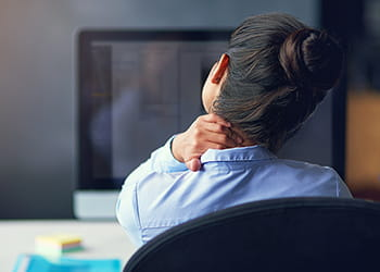 Woman working on a computer with a sore neck