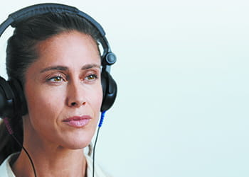 Woman wearing headphones - Audika Hearing - Hearing Aids, Equipment & Services