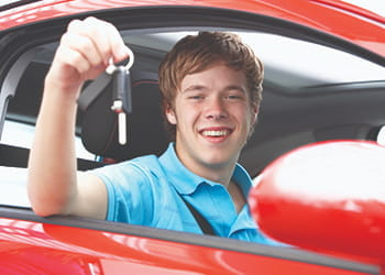Young man in a car holding car keys