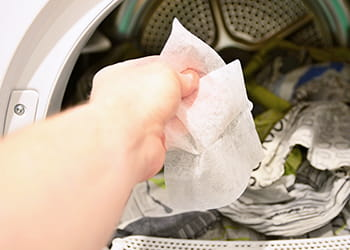 Hand removing tumble dryer sheet from tumble dryer