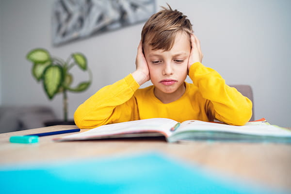 Young boy looking stressed by his homework