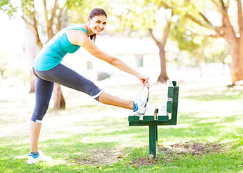 Woman stretchin on park bench