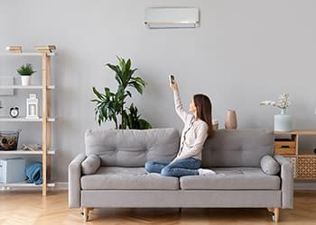 Woman in cosy home adjusting air conditioner