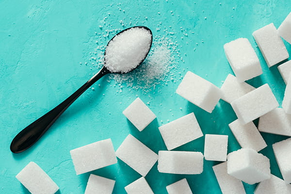 sugar cubes and spoon of sugar on turquoise background