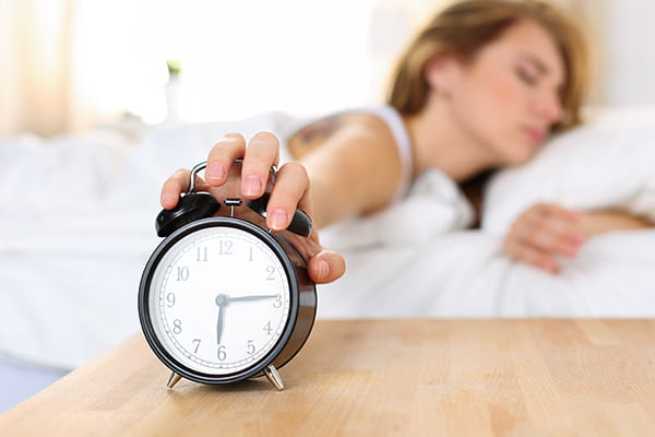 Woman waking up and turning off alarm clock