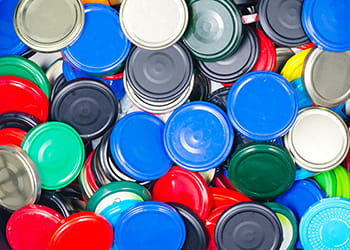 Pile of colourful metal container lids