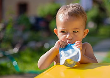 Little boy sucking on yoghurt pouch