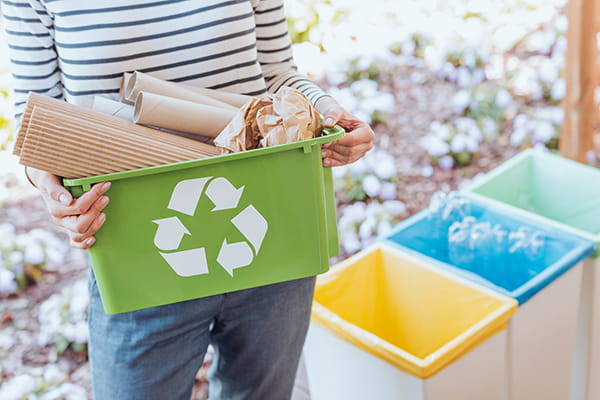 Lady carrying tray of recycling items