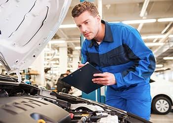 Mechanic looking under a car hood