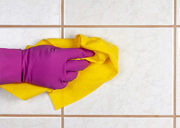 Hand cleaning tiles with a cloth
