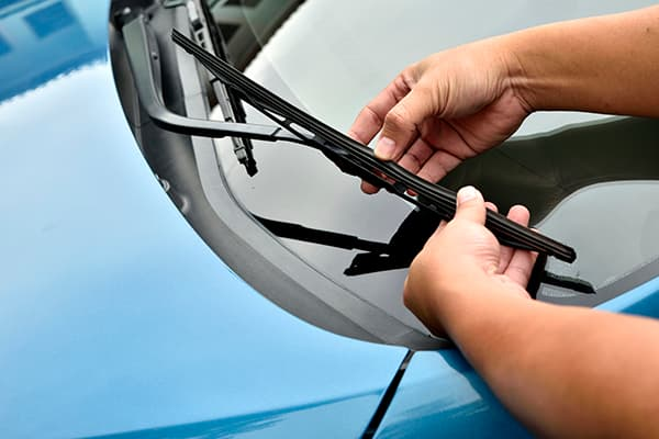 Car wiper blades being replaced