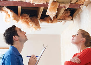 Couple looking at a ceiling that has collapsed