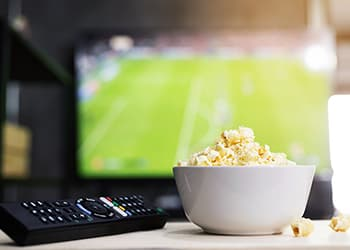 Bowl of popcorn and TV remote in front of a TV