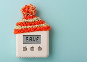 Digital thermostat wearing a red and yellow striped woolly hat