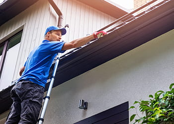 Man standing on a ladder cleaning the gutters