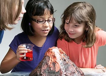 Three friends doing a volcano science project