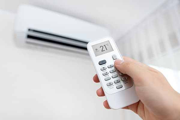 Hand holding an air conditioner remote control