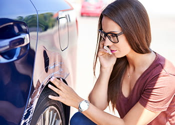 Lady looking at scratches on her car
