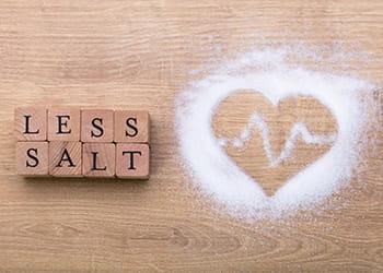 Heart made from salt and blocks beside reading Less Salt