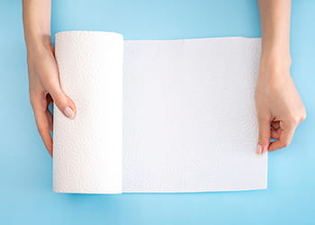 Hands holding paper towel on a blue background