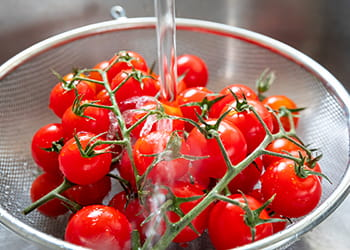 Cherry tomatoes being washed in a sieve