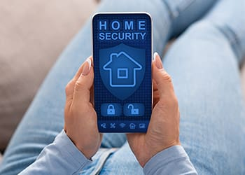 Man with a smartphone for his home security system