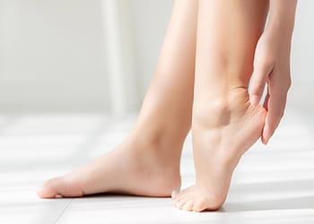 person applying cream to heels