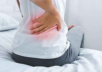 person with back pain holding lower back
