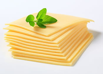 stack of sliced cheese with basil leaves on top