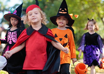 Kids outside trick-or-treating in Halloween costumes