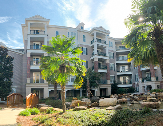 spring harbor senior living apartments among trees and a large pond surrounding by rocks