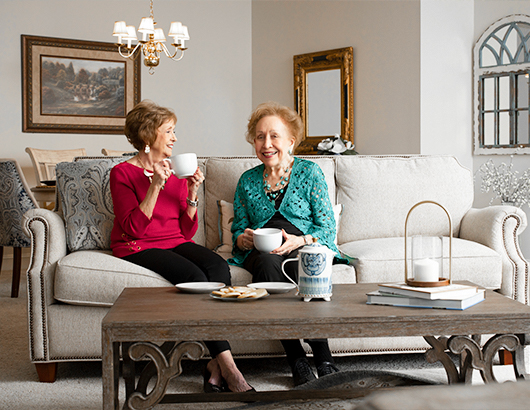 two senior women sitting on  a couch having tea and chatting