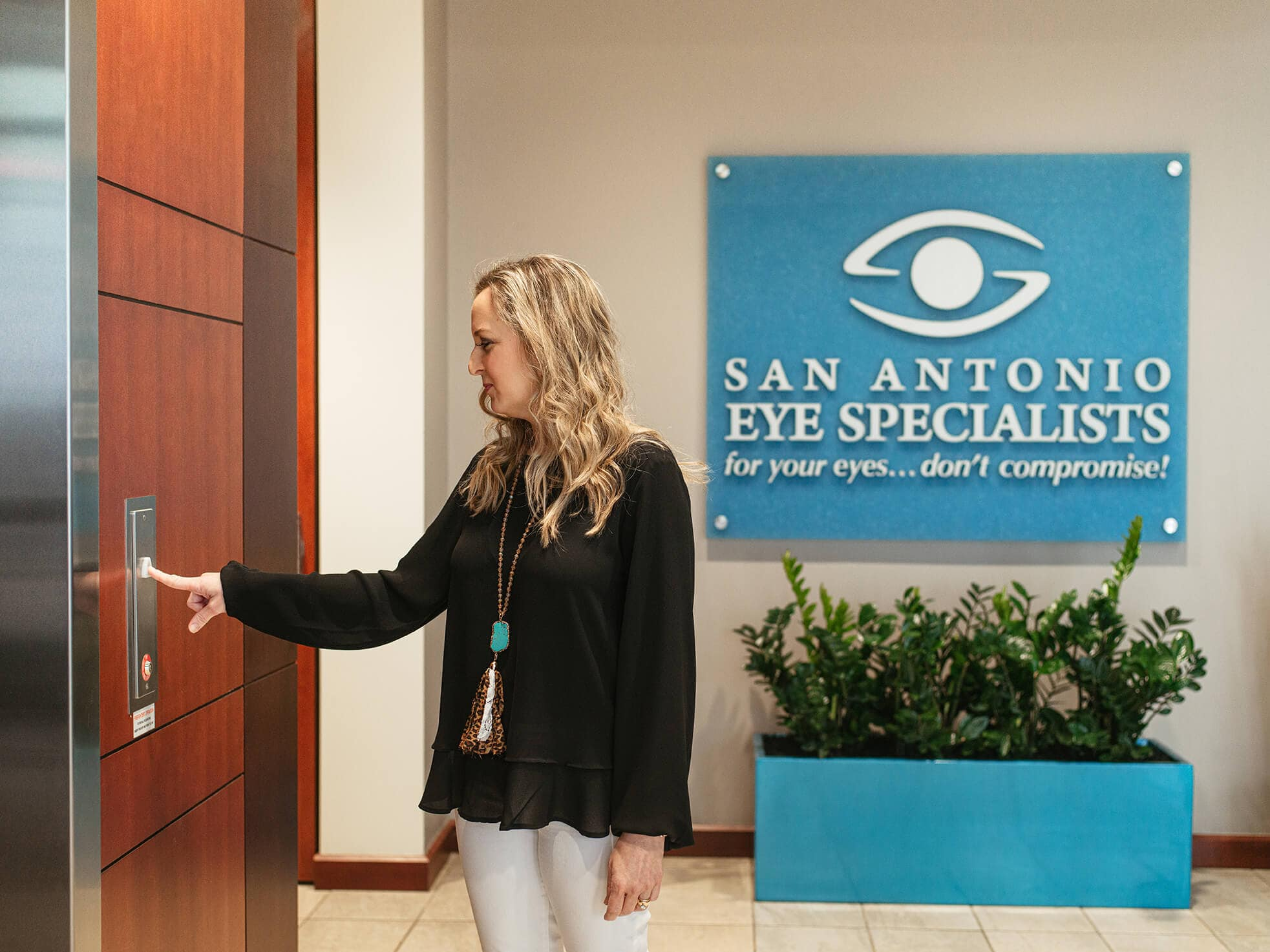 Woman at elevators in front of San Antonio Eye Specialists sign.