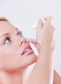 Woman applying eye drops to eyes