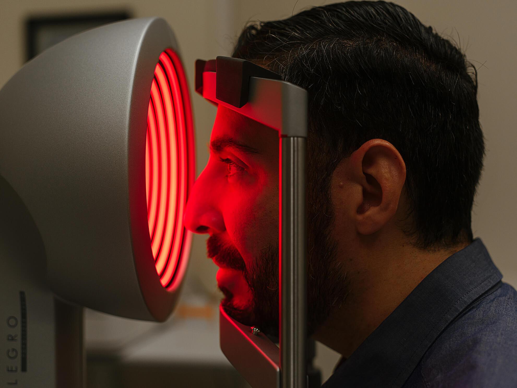 Machine examining a man's eyes