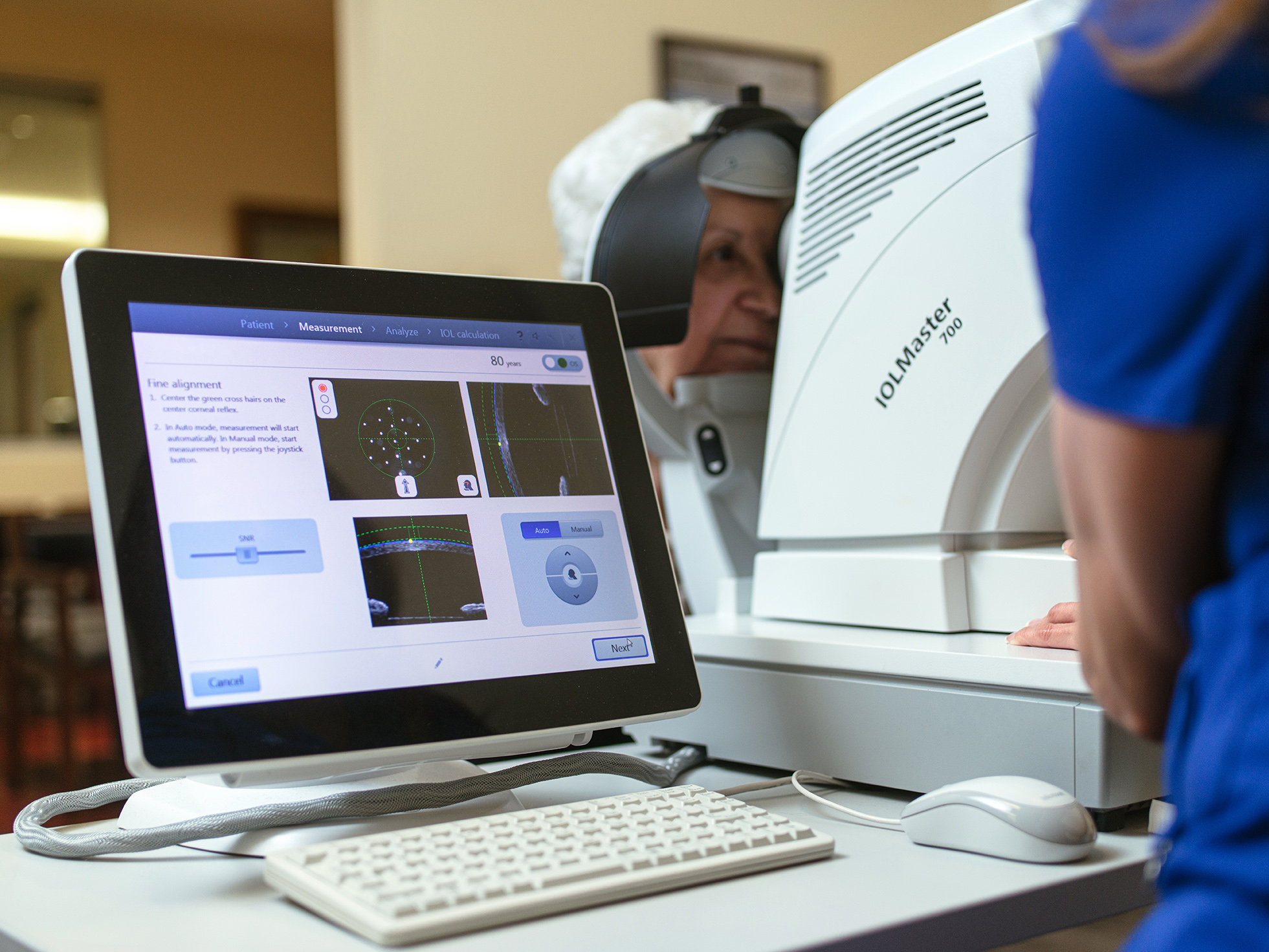 Screen showing eye scan with elderly woman at machine behind