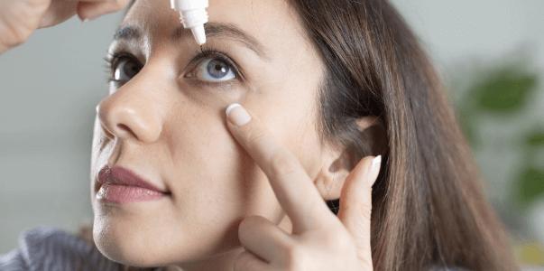 Woman applying eye drops.