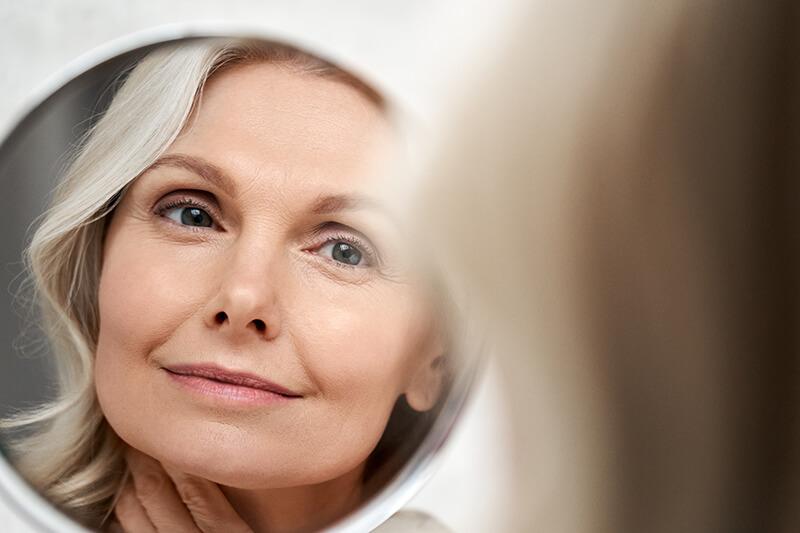 Woman examining eyes in the mirror
