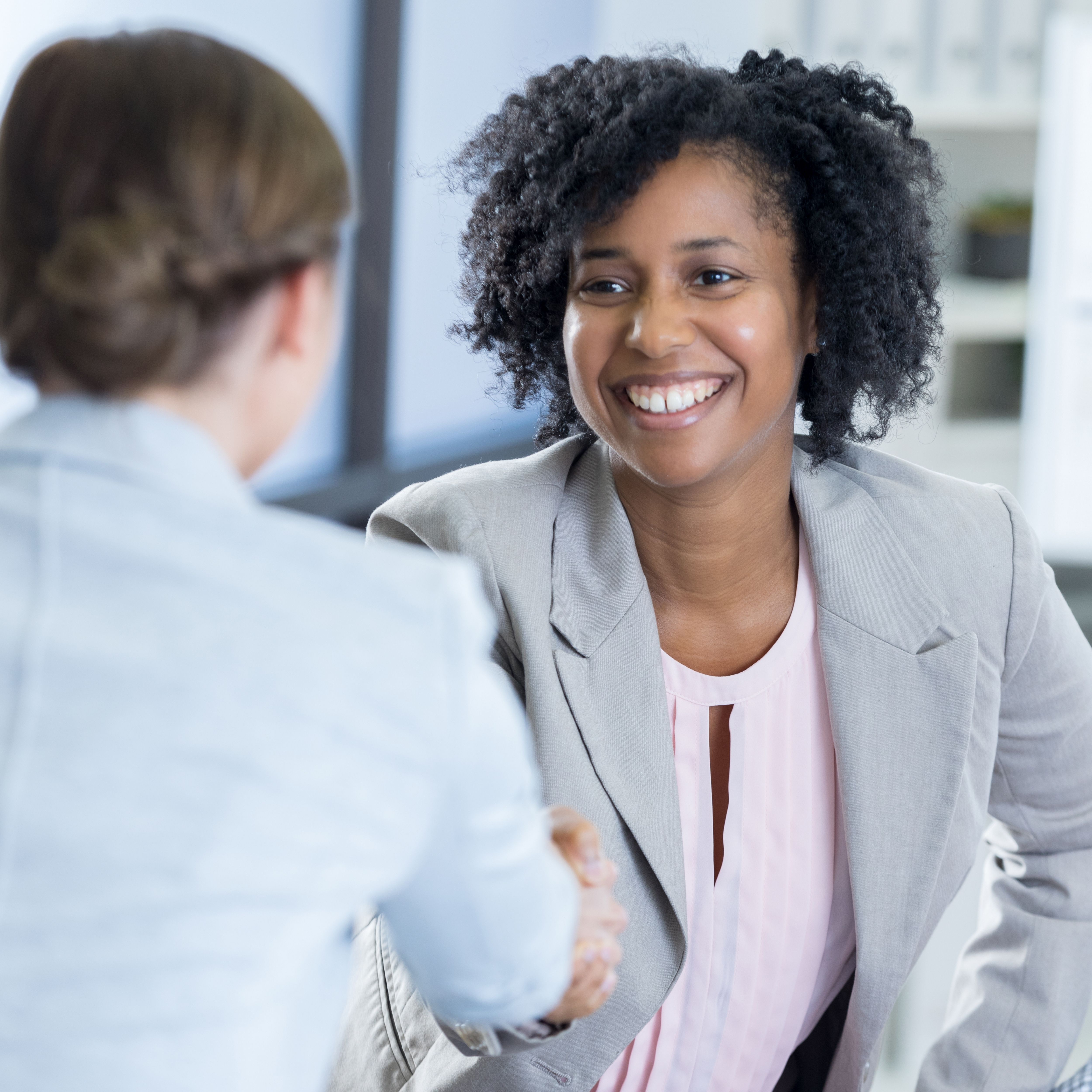 a woman with glorious har is welcoming a client