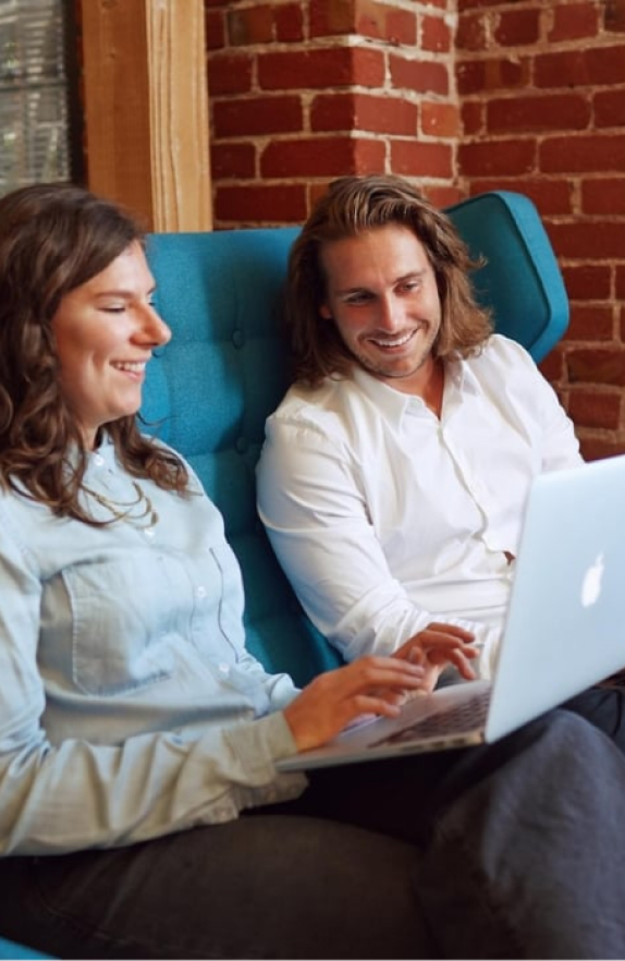 Two people collaborating on laptop