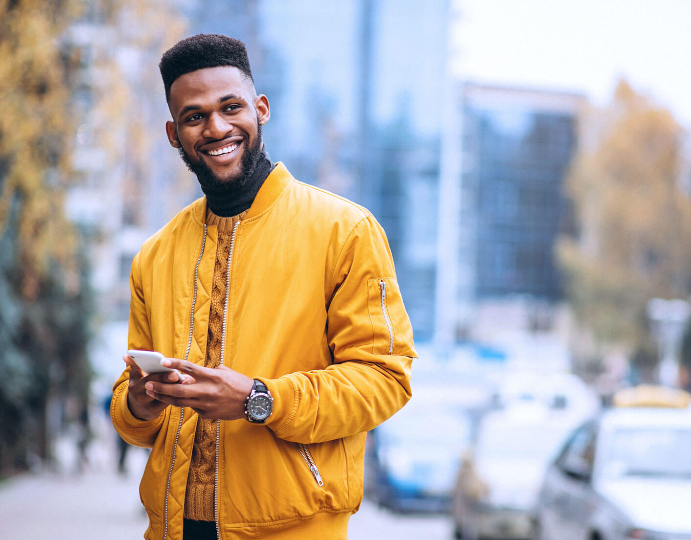 black man in orange jacket outside holding mobile phone looking off screen