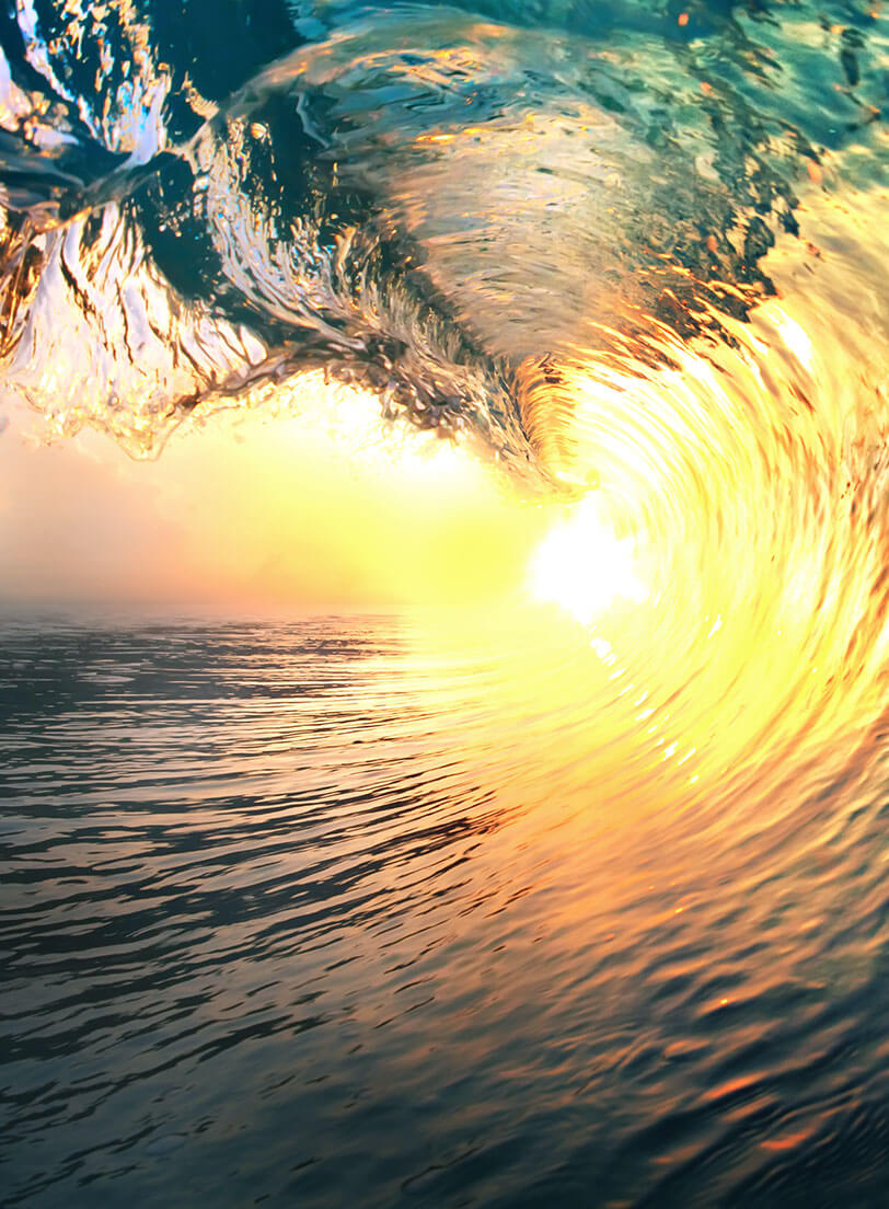 crashing wave with sunset in the curl of the wave