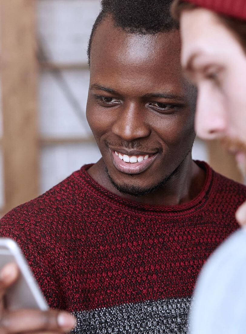 black man looking at mobile phone