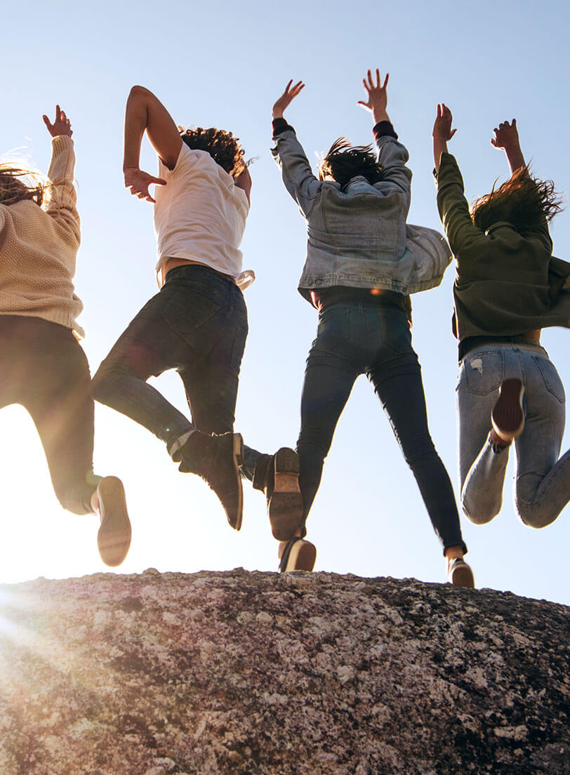 Group of young people jumping with backs to camera on top of a hill