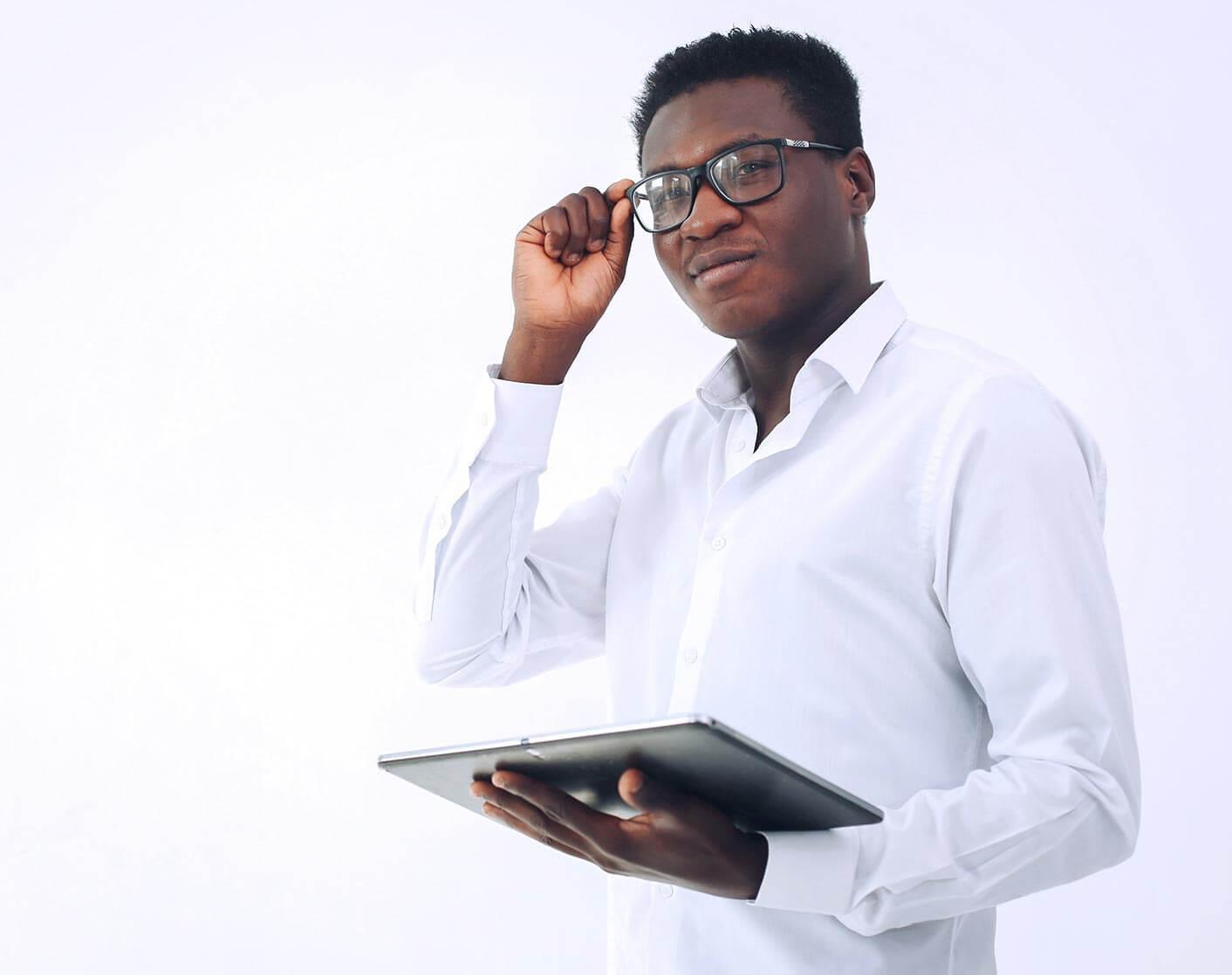 black man in white shirt adjusting glasses while holding tablet