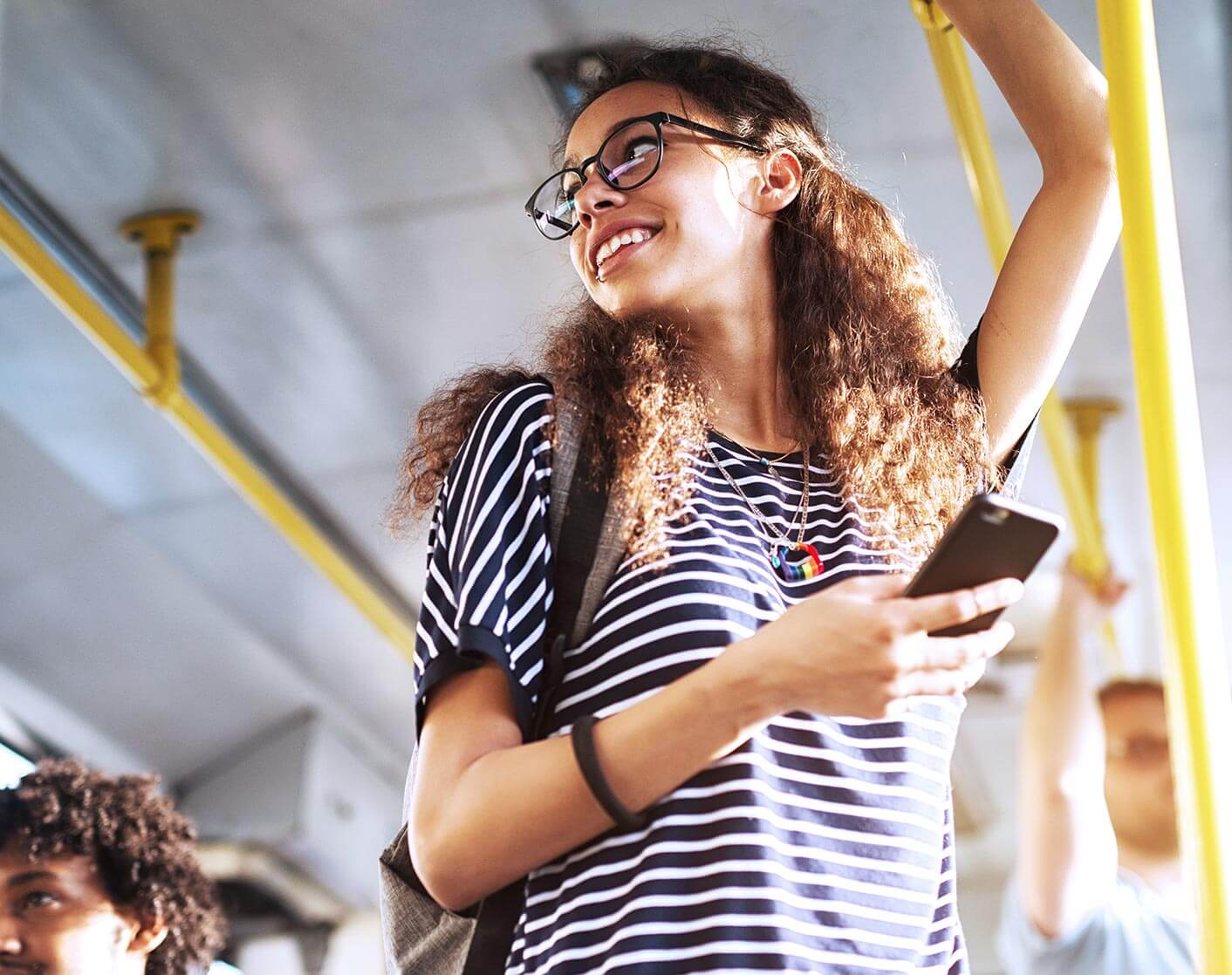 white woman standing on bus holding mobile phone looking over her shoulder away from camera