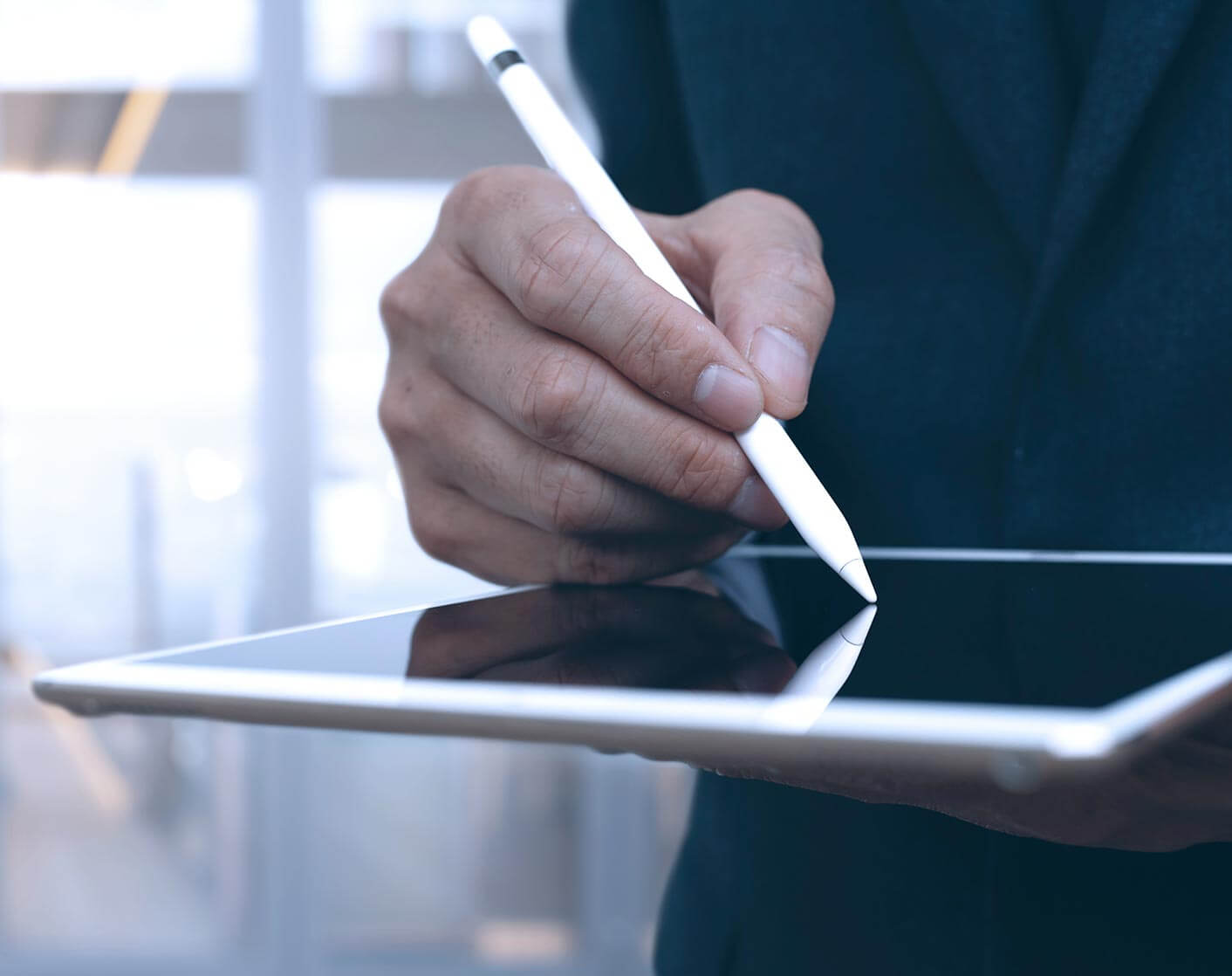 man holding tablet using a white stylus