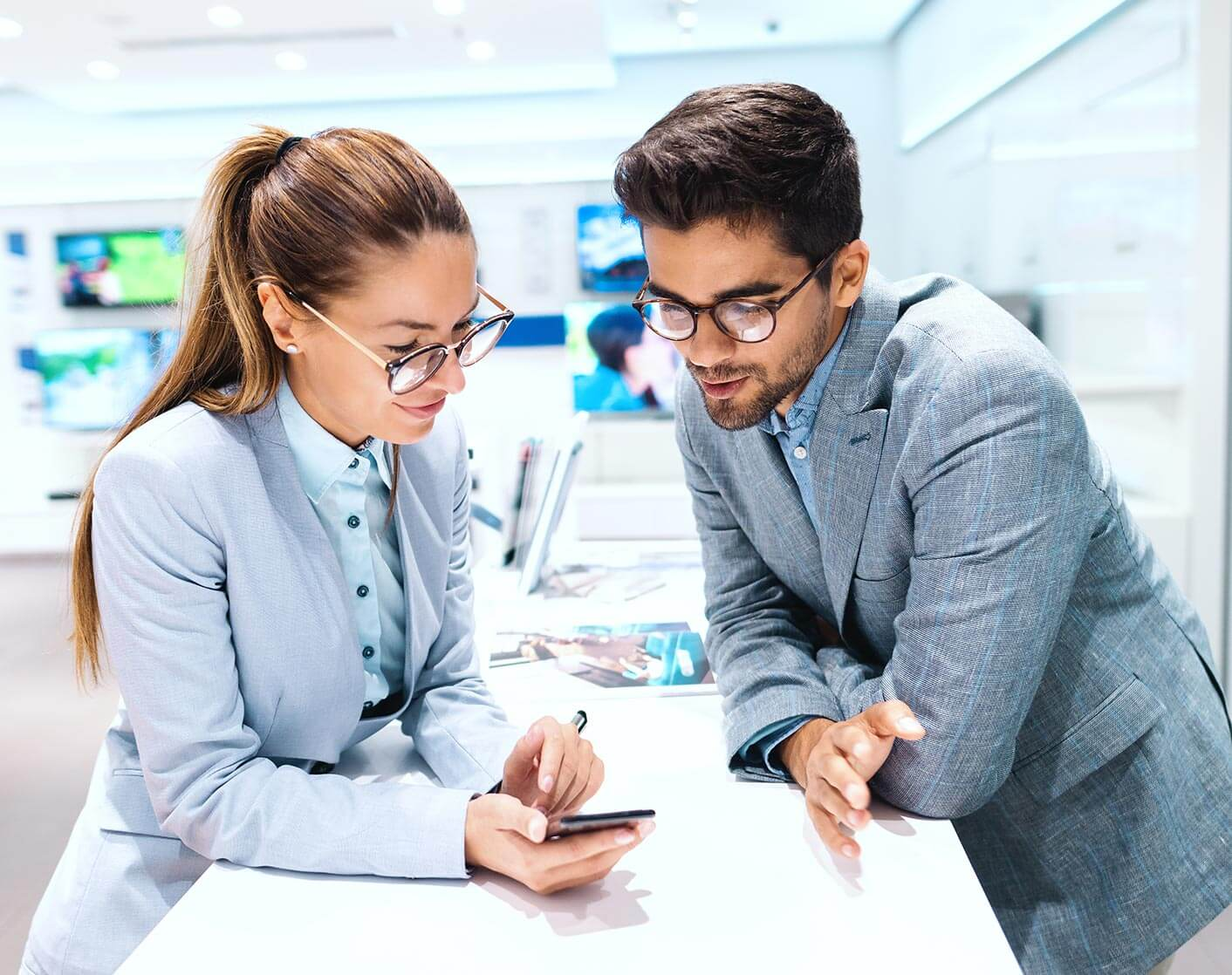professional man and woman leaning on sales counter looking at a mobile phone