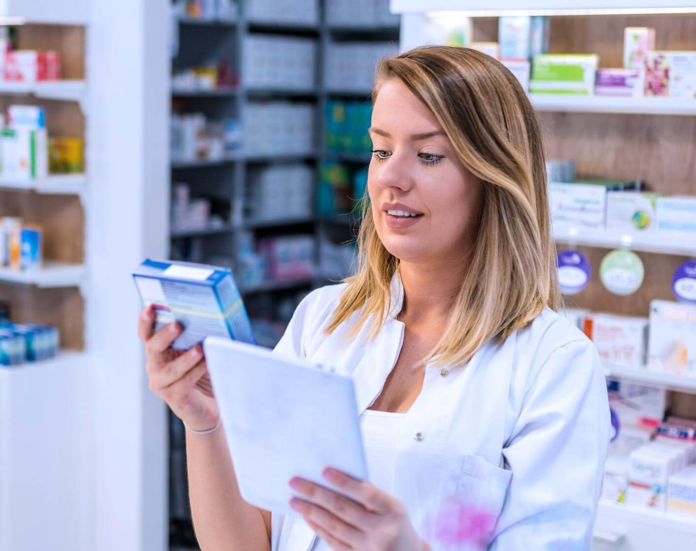 blonde female pharmacist reviewing a prescription