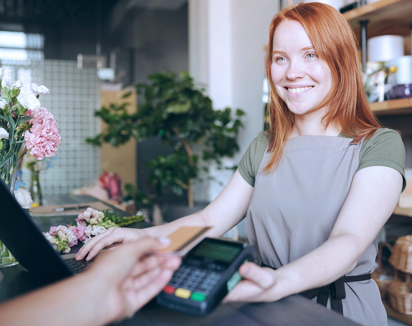 female redheaded store clerk passing debit pin pad to customer in foreground
